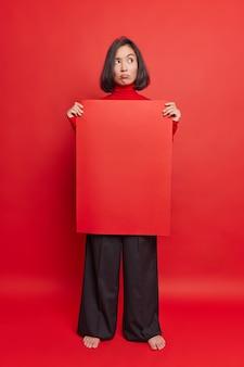 Foto de corpo inteiro de uma mulher asiática morena pensativa e descontente usando calças pretas e um outdoor em branco com espaço de cópia para seu conteúdo de publicidade e pés descalços contra uma parede vermelha vívida.