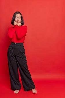 Foto de corpo inteiro de uma mulher asiática pensativa com cabelo escuro, com as mãos no queixo, olhando para algo interessante, usa calça preta de gola alta solta fica com os pés descalços dentro de casa contra a parede vermelha