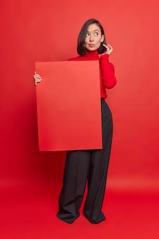 Foto de corpo inteiro de uma mulher asiática pensativa segurando um banner para seu conteúdo de publicidade ou texto promocional usando gola alta e calças formais pretas poses contra a parede vermelha
