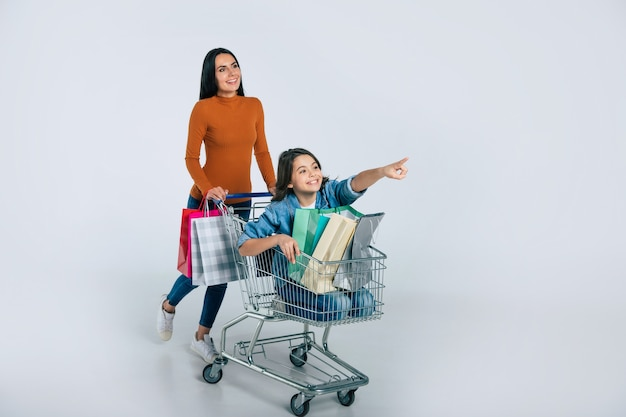 Foto de corpo inteiro de uma mulher atraente em roupas casuais, que está empurrando um carrinho de compras com a filha, que está apontando para a frente, e três sacolas de compras dentro dele.