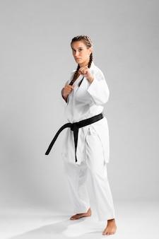 Foto de corpo inteiro de uma mulher com faixa preta e quimono praticando karatê