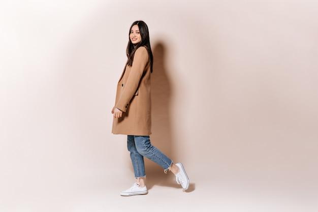 Foto de corpo inteiro de uma mulher com um casaco elegante e jeans