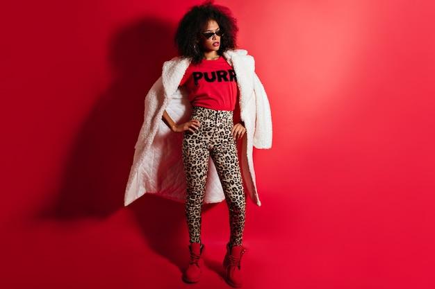 Foto de corpo inteiro de uma mulher confiante em calças elegantes
