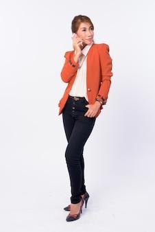 Foto de corpo inteiro de uma mulher de negócios asiática madura pensando enquanto fala ao telefone