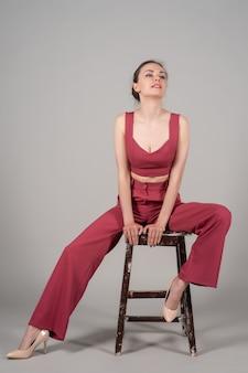 Foto de corpo inteiro de uma mulher de negócios chique atraente sentada em uma cadeira usando um terno vermelho de salto alto isolado fundo cinza