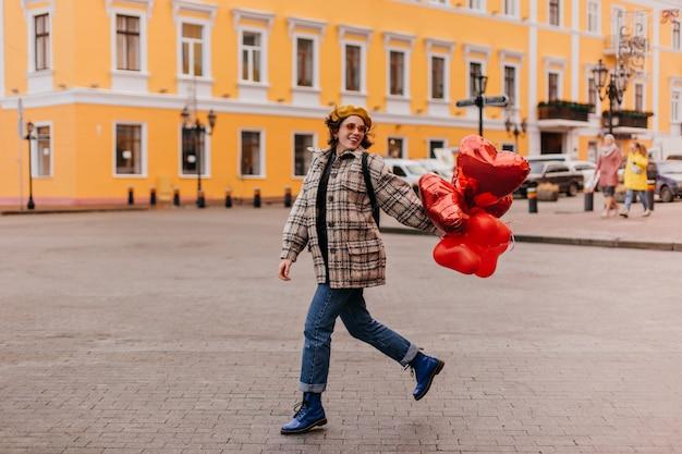 Foto de corpo inteiro de uma mulher elegante caminhando com sapatos azuis dr. martins e uma jaqueta de tweed grande