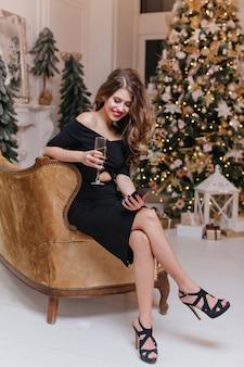 Foto de corpo inteiro de uma mulher em um elegante traje totalmente preto, olhando para as mensagens no telefone. morena sentada em um lindo sofá macio contra uma árvore de natal