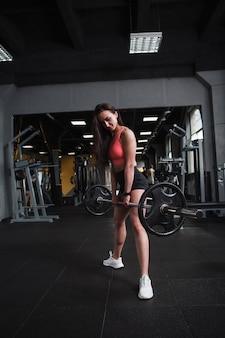 Foto de corpo inteiro de uma mulher fitness fazendo agachamentos de sumô com barra