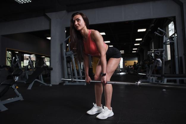Foto de corpo inteiro de uma mulher fitness se exercitando com barra