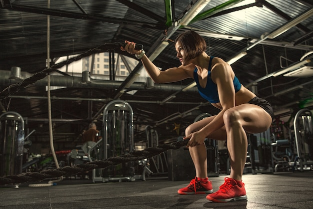 Foto de corpo inteiro de uma mulher jovem fitness em equipamento de treino exercitar-se com cordas de batalha no ginásio