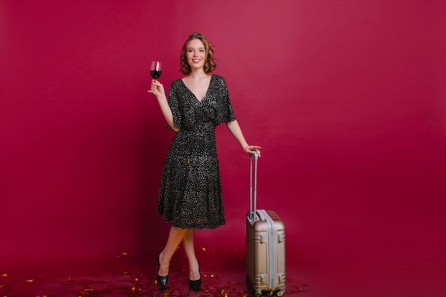 Foto de corpo inteiro de uma mulher loira feliz em pé com as pernas cruzadas e segurando uma mala