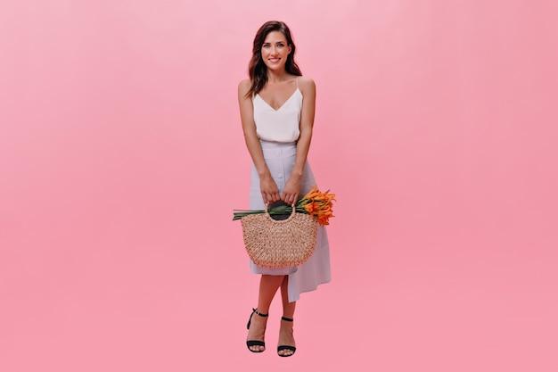 Foto de corpo inteiro de uma mulher segurando uma bolsa com flores