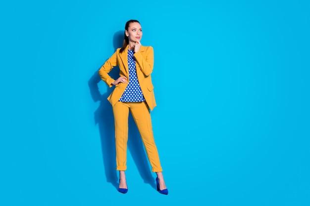 Foto de corpo inteiro de uma senhora atraente e simpática trabalhadora, olhar para o lado, espaço vazio, braço no queixo, usar blazer amarelo terno calça calça blusa pontilhada calçado de salto alto isolado fundo de cor azul brilhante