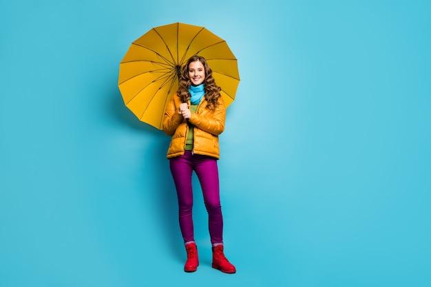 Foto de corpo inteiro de uma senhora bonita e encaracolada segurando guarda-chuva brilhante, aproveite o dia ensolarado de primavera, caminhada na rua, use sobretudo amarelo, lenço azul, calças violeta, sapatos vermelhos, parede de cor azul isolada