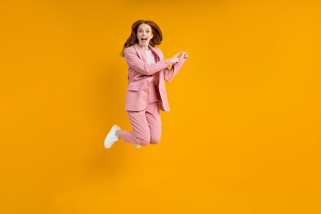 Foto de corpo inteiro de uma senhora caucasiana engraçada em um terno rosa pulando alto, veja os preços baixos de compra ...