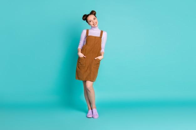 Foto de corpo inteiro de uma senhora encantadora e radiante se sentindo ótimo tempo incrível passeio de fim de semana no parque braços bolsos usar roupa de outono sapatos violeta suéter vestido de veludo marrom isolado fundo de cor turquesa