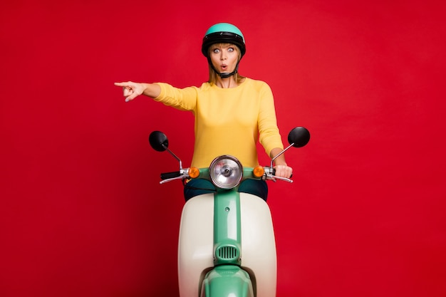 Foto de corpo inteiro de uma senhora engraçada que dirige o espaço vazio de dedo direto de bicicleta