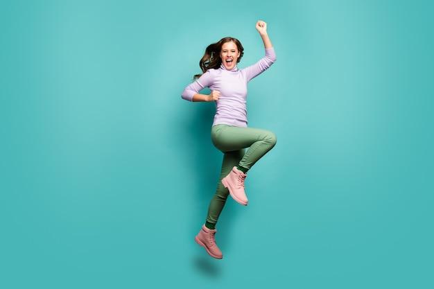 Foto de corpo inteiro de uma senhora louca pulando alto regozijando-se preto sexta-feira vendas shopping center abrindo os punhos levantados e usando jumper roxo calça calça verde isolada cor pastel azul
