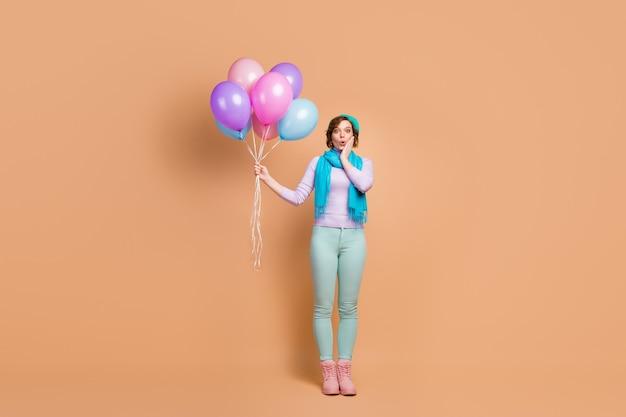 Foto de corpo inteiro de uma senhora muito chocada carregando muitos balões de ar inesperada festa surpresa usar jumper lilás calças verdes botas boina cachecol isolado fundo de cor bege
