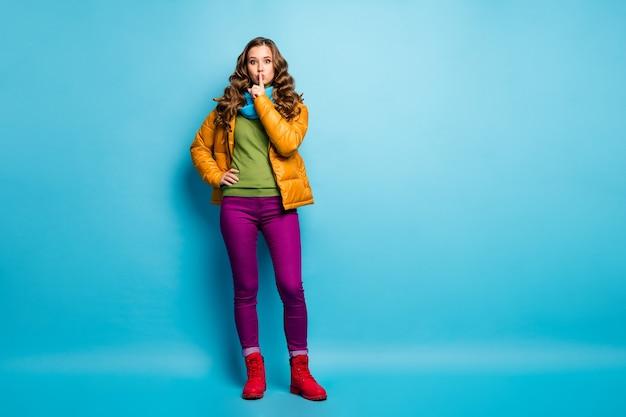 Foto de corpo inteiro de uma senhora muito encaracolada segurando o dedo nos lábios, pedindo para manter o segredo na privacidade, usar casaco amarelo casual lenço calça violeta sapatos vermelhos parede azul isolada