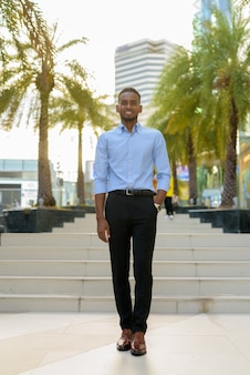 Foto de corpo inteiro do belo empresário negro africano ao ar livre na cidade durante o verão, sorrindo e andando na vertical.