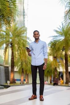 Foto de corpo inteiro do belo empresário negro africano ao ar livre na cidade durante o verão, sorrindo e segurando o telefone na vertical.