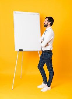 Foto de corpo inteiro do empresário dando uma apresentação no quadro branco sobre amarelo isolado na posição lateral