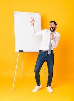 Foto de corpo inteiro do empresário dando uma apresentação no quadro branco sobre amarelo isolado nervoso e assustado