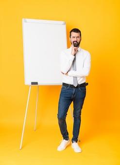 Foto de corpo inteiro do empresário dando uma apresentação no quadro branco sobre amarelo isolado, olhando de frente