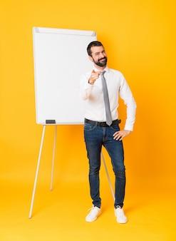 Foto de corpo inteiro do empresário dando uma apresentação no quadro branco sobre dedo amarelo isolado para você com uma expressão confiante