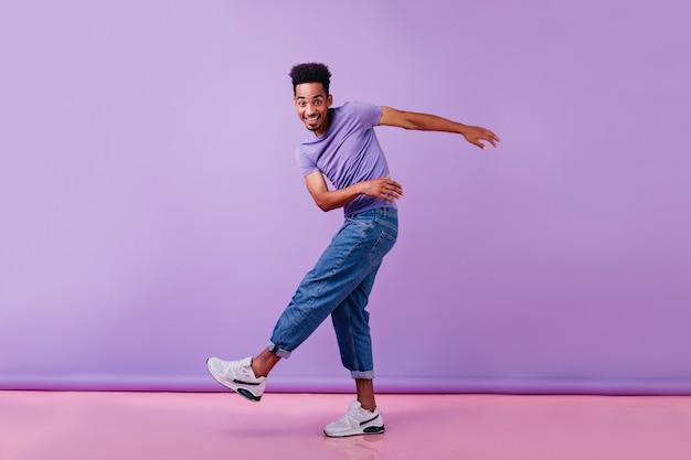 Foto de corpo inteiro do homem africano feliz dançando com um sorriso sincero. modelo masculino de jeans e camiseta roxa se divertindo.
