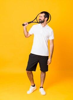 Foto de corpo inteiro do homem ao longo da parede amarela isolada, jogando tênis e olhando para cima