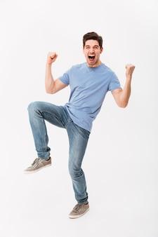 Foto de corpo inteiro do homem feliz 30 anos em jeans e camiseta casual, regozijando-se com os punhos cerrados, isolados sobre a parede branca