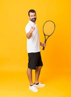 Foto de corpo inteiro do homem sobre amarelo isolado jogando tênis e apontando para a frente