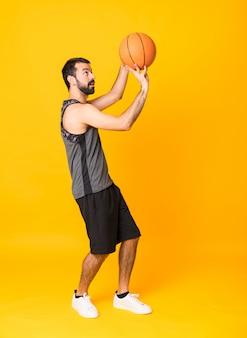 Foto de corpo inteiro do homem sobre fundo amarelo isolado jogando basquete