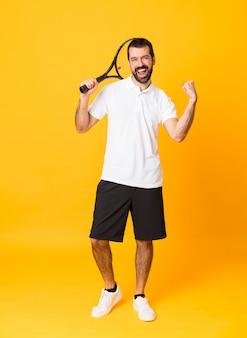Foto de corpo inteiro do homem sobre fundo amarelo isolado, jogando tênis e comemorando uma vitória