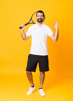 Foto de corpo inteiro do homem sobre fundo amarelo isolado, jogando tênis e fazendo sinal de ok