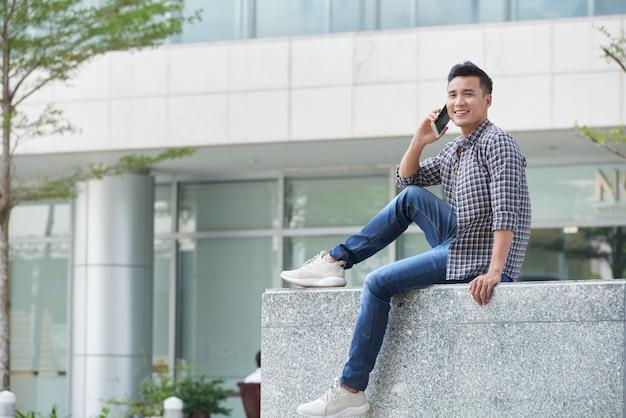 Foto de corpo inteiro do jovem asiático sentado no mármore ao ar livre, falando ao telefone