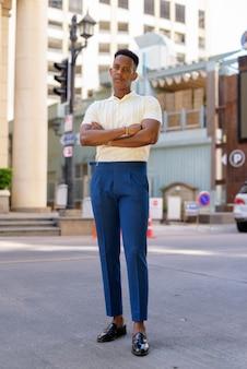 Foto de corpo inteiro do jovem empresário africano ao ar livre nas ruas da cidade, olhando para a frente com os braços cruzados