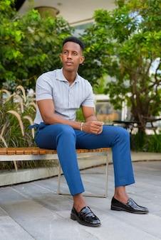 Foto de corpo inteiro do jovem empresário africano vestindo roupas casuais e sentado no banco do parque enquanto pensa
