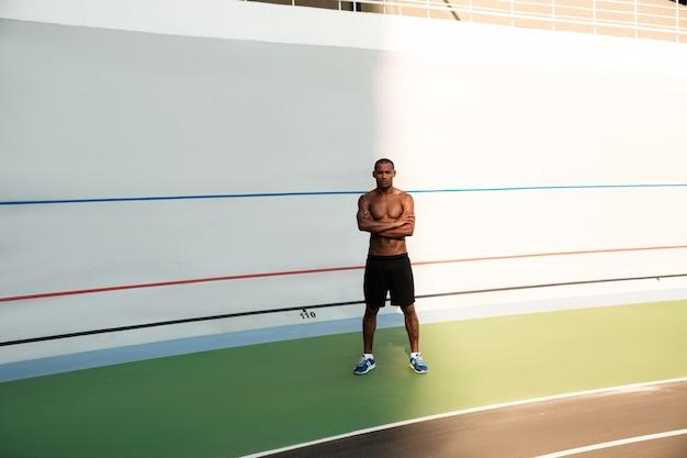 Foto de corpo inteiro do jovem homem africano de esportes, em pé com as mãos cruzadas