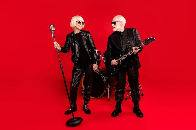 Foto de corpo inteiro duas pessoas esposa marido aposentado aposentado fã de rock mulher cantor solo homem tocar guitarra baixo olhar desfrutar estúdio tour garagem prática evento isolado brilhante brilho cor de fundo
