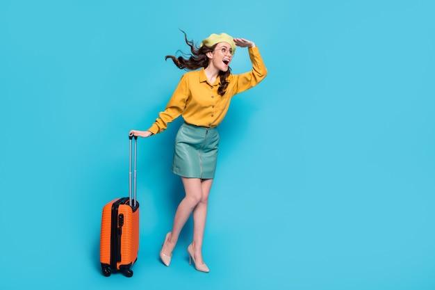Foto de corpo inteiro garota animada turista segurar mão cabeça ver avião corte de cabelo ondulado voar golpe segurar bagagem vestir blusa amarela estilo estilete na moda elegante isolado sobre fundo de cor azul