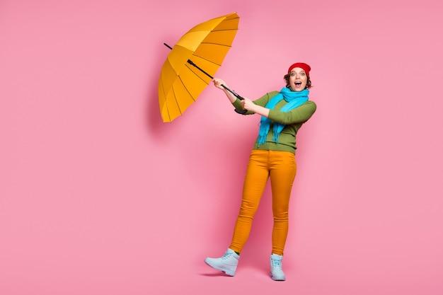 Foto de corpo inteiro garota animada, viagem, viagem, seu brilho guarda-chuva voar vento ar, ela tenta pegar grito uau omg usar capacete vermelho azul pulôver calças de inverno isolado parede cor de rosa