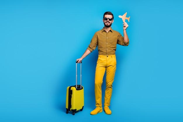 Foto de corpo inteiro homem barbudo positivo aproveite fins de semana de turismo segurar papel de parede laranja bonde de avião viajar ar primeira classe usar roupa xadrez calças brilhantes sapatos esportivos isolado cor azul