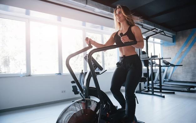 Foto de corpo inteiro. linda mulher loira no ginásio em seu tempo de fim de semana.