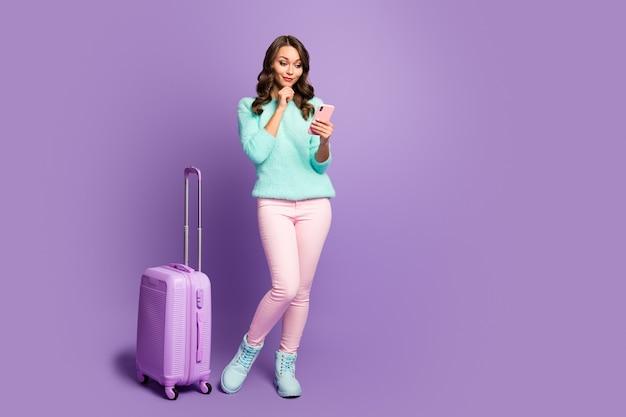 Foto de corpo inteiro menina curiosa chegar férias no aeroporto usar smartphone chamada serviço de táxi usar calça pastel rosa azul-celeste fofo fuzzy jumper macio
