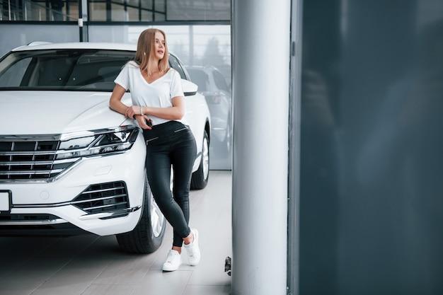 Foto de corpo inteiro. menina e carro moderno no salão. durante o dia dentro de casa. comprando novo veículo