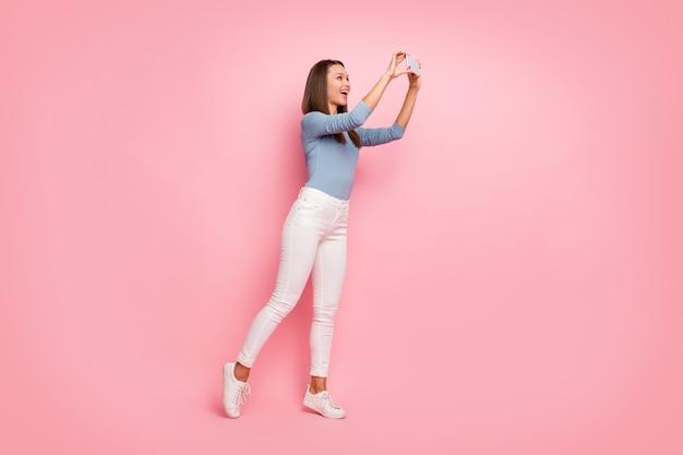 Foto de corpo inteiro virada de alegre positiva fofa linda e doce namorada sorrindo, fotografando o espaço vazio em um suéter azul com fundo de cor pastel isolado