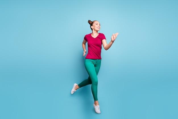 Foto de corpo inteiro virada de corpo inteiro de namorada alegre positiva fofa bonita vestindo calças correndo pulando aspirando chegar a tempo isolada sobre parede azul pastel